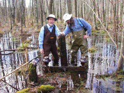 Mead and Mike Spadafora with a 1912 crossarm they  discovered in a swamp in upstate New York.